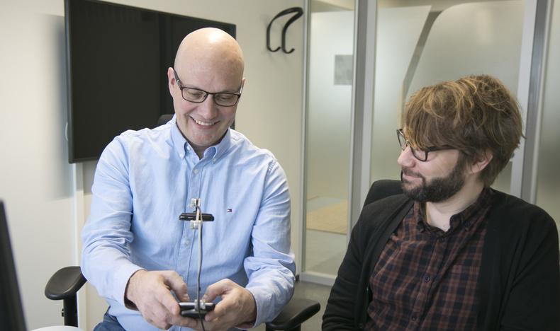 Forskningschef Raino Vastamäki testar en webbtjänst med en mobiltelefon. Ansluten till telefonen finns en kamera som spelar in anvädningen av tjänsten. Bredvid tillgänglighetsexpert Timo Övermark.
